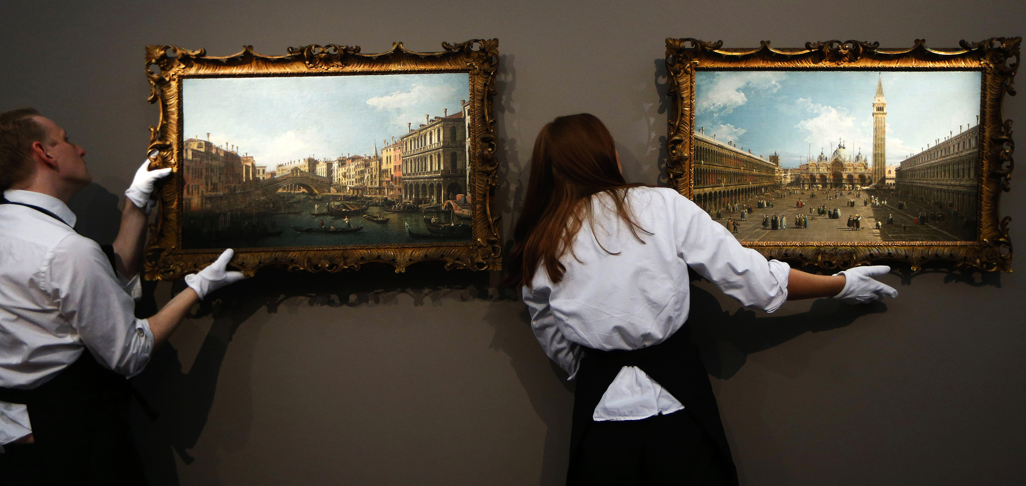 Sotheby's employees hang up the paintings 'A View of the Grand Canal and Rialto Bridge', left, and 'A View of the Piazza San Marco looking East towards the Basilica' by Canaletto on display at the auction house in London, Monday, Dec. 2, 2013. The paintings are to be auctioned as a pair in 'Old Master and British Paintings' sale on Dec. 4 with an estimated price of 8 to 12 million pounds (US$12.44 to 18.66 million or 9.3 to 13.94 million euro). (AP Photo/Sang Tan)